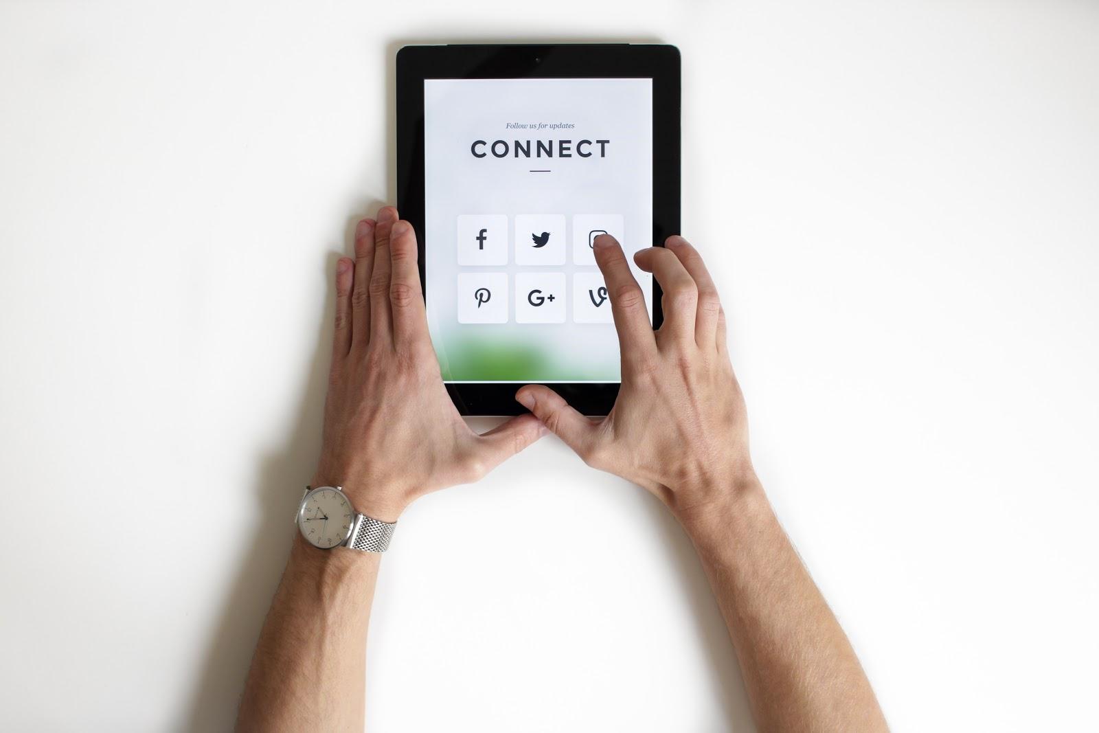 Homem mexendo em iPad com ícones de redes sociais